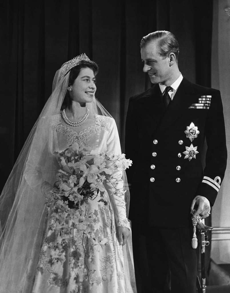 Think you know what Queen Elizabeth II and Prince Philip's wedding was really like after watching The Crown? Sure, the Netflix drama sticks pretty close to history, but there are actually a few pretty big differences between the show and what the royal couple's nuptials were really like. Elizabeth and Philip's big day was one of the first in a long line of high-profile royal unions that the public flocked to the streets to witness, like Grace Kelly and Prince Rainier III of Monaco, and later on, Princess Diana and Prince Charles. Though their November 1947 wedding was spectacular in some ways, they also had one of the most low-key royal weddings due to war time austerity. Let's dive into the event, from start to finish.