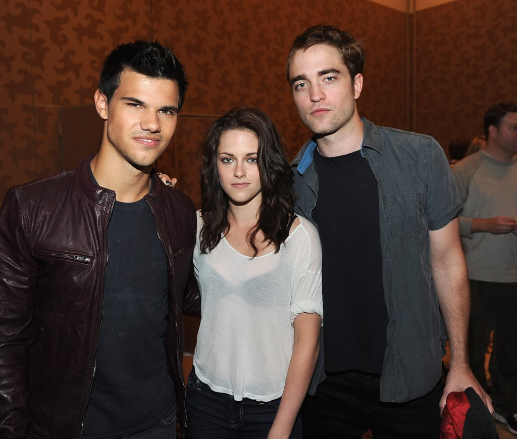 "Robert Pattinson teamed up with his Twilight buddies today for Comic-Con in San Diego. He posed with Kristen Stewart and Taylor Lautner before a press conference at the Hilton Bayfront Hotel to chat up Breaking Dawn: Part I. Robert showed off the interesting haircut he got for his most recent film, Cosmopolis — he still rocked the half-shaved, half-regular 'do! Kristen also went for a unique look by pairing her dark bra with a light tee. Some of their costars like Nikki Reed and Ashley Greene rose early this morning to meet fans outside before the interviews commenced. Buzz is in Southern California live tweeting from Comic-Con, sharing quips from Rob like that he hopes to see a film in the series called ""breakfast time."" Ashley and Nikki spoke before Rob, Kristen, and Taylor and revealed a couple Breaking Dawn teasers."