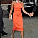 Victoria Beckham wore an orange dress.