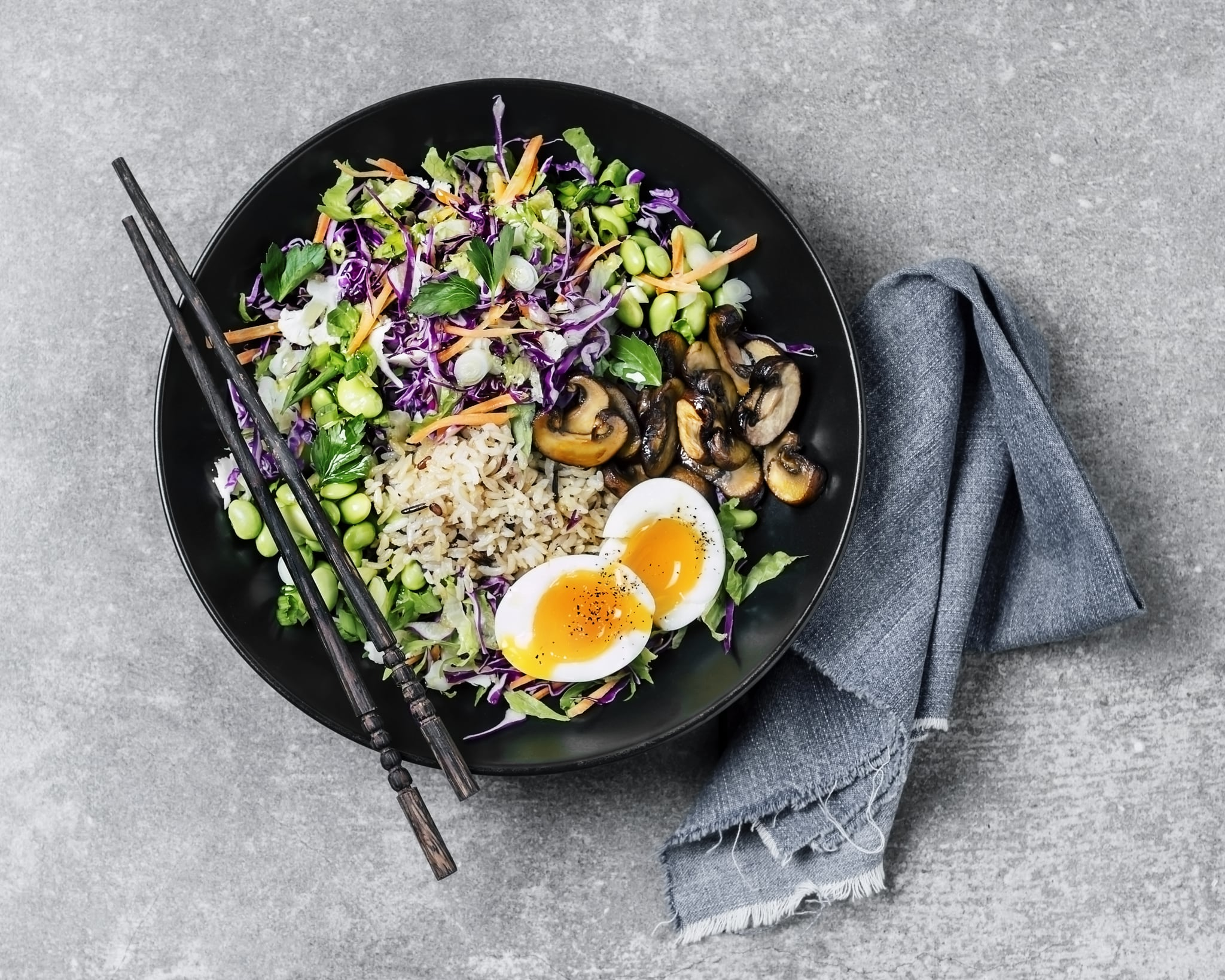 A bowl of fresh salad with fried rice, and boiled eggs on gray background