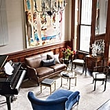 The walls in the music room are lined with elegant and sound-insulating fabric walls. A Yamaha piano is the focus of the room, but an oversize Anna Lapin painting steals the spotlight.