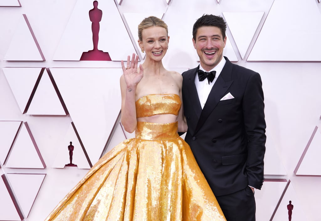 Carey Mulligan has a big night ahead of her at the Oscars, and her husband, Marcus Mumford, is right by her side as her biggest cheerleader. Carey, who's nominated for best actress for her role in Promising Young Woman, looked like an actual Oscar in a Disney-esque gold ballgown, while Marcus let his wife shine in a classic black tux. The outing marks a rare red carpet sighting for the low-key couple, who, in case you forgot, have been married for nearly a decade. Though the two married in 2012, their love story actually began when they were children attending the same church camp. Throughout the years, the actress and the Mumford & Sons lead singer sweetly stayed in touch as pen pals and eventually rekindled their relationship as adults. While they often support each other at their various gigs and events, we don't often get to see the two in public together, so be sure to get a close look ahead at the couple arm in arm at Sunday night's Oscars.
