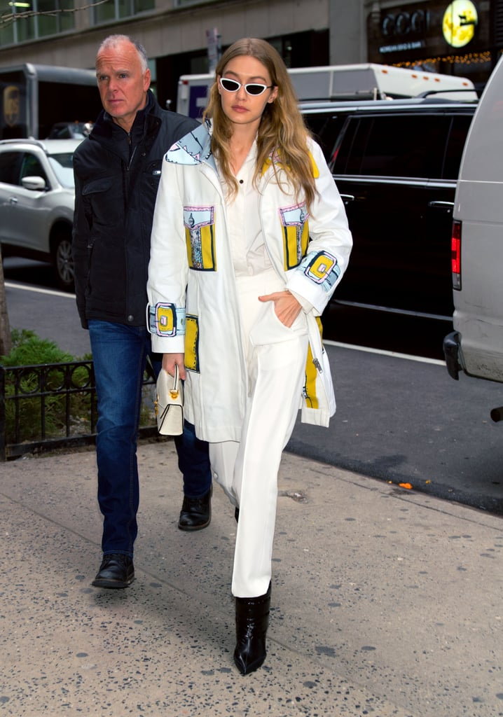 The model wore a pop-art inspired white coat over her ARIAS top and bottom at NYFW. She accessorized with Linda Farrow sunglasses and black booties.