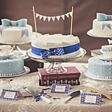 Although there's more than one cake on this dessert table, our eyes are on the bright blue bow-wrapped stunner in the middle. A delicate pearl edge and fun banner are all it takes to make this one swoon-worthy cake