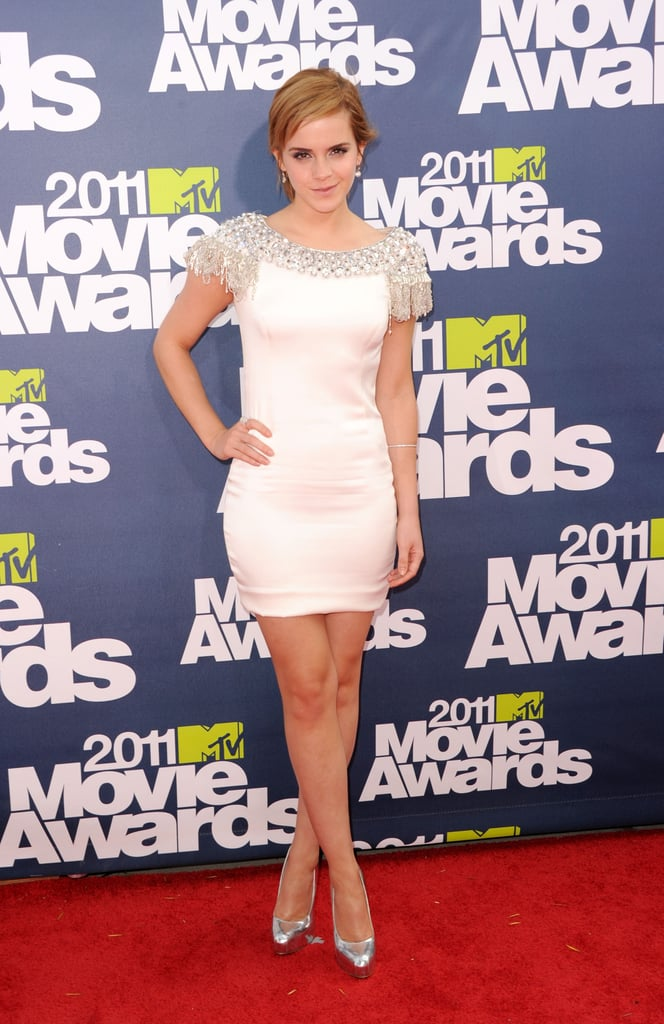 Emma Watson stepped onto the red carpet at the MTV Movie Awards in LA tonight, showing off her legs in a sexy white mini from Marchesa. The Harry Potter actress is up for multiple awards tonight. She's going up against another Emma, Emma Stone, Twilight's Kristen Stewart, Jennifer Aniston, and Natalie Portman for the hotly contested best female performance golden popcorn. Emma and her costar Daniel Radcliffe are also nominated in the best kiss category, though they'll have to beat two-time winners Robert Pattinson and Kristen Stewart if they're going to win that race. Stay tuned for more photos and news as we update live from inside the show throughout the night, and make sure to check out FabSugar and BellaSugar's love it or hate it polls!