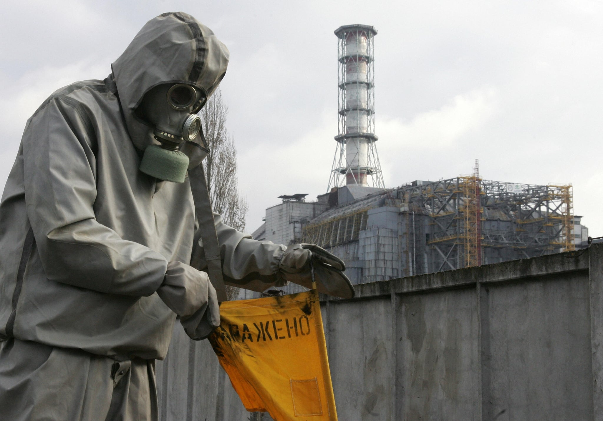 Chernobyl, UKRAINE:  A rescue worker sets flag signalling radioactivity in front of Chernobyl nuclear power plant during a drill organised by Ukraine's Emergency Ministry 08 November 2006. Employees and rescue workers improved their reactivity in case of a collapse of the sarcophagus covering the destroyed 4th power block. AFP PHOTO/ SERGEI SUPINSKY  (Photo credit should read SERGEI SUPINSKY/AFP/Getty Images)