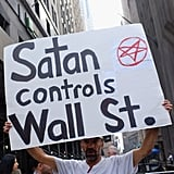 "A protestor holds a sign that says ""Satan controls Wall St."""