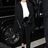 Kim Kardashian took on Paris in a fittingly chic black and white ensemble, including black leather gloves and a black fur collar.