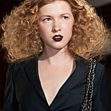 Maison Anoufa added a pop of color with spray-painted parts on the Haute Couture runway in Paris. The lips were dark purple matched with red liner to offset the dramatically curled coifs.