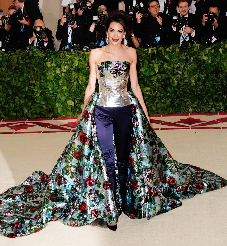 """As one of the cohosts for the 2018 Met Gala, Amal Clooney pulled up to the red carpet going in a direction she's never gone before: the """"pants gown."""" Wearing a stunning ensemble by Richard Quinn, the mom of two emanated floral and metallic excellence. Hubby George Clooney went for his classic black and white tuxedo look, ensuring all eyes were on his beautiful wife. From the front, it looks like Amal is wearing a floral bustier and navy pants, but from the back, her floral train looks entirely different. Read on to see the couple's stunning 2018 Met Gala appearance.      Related:                                                                                                           Every Look at This Year's Met Gala Was Bold Enough to Leave an Impression"""