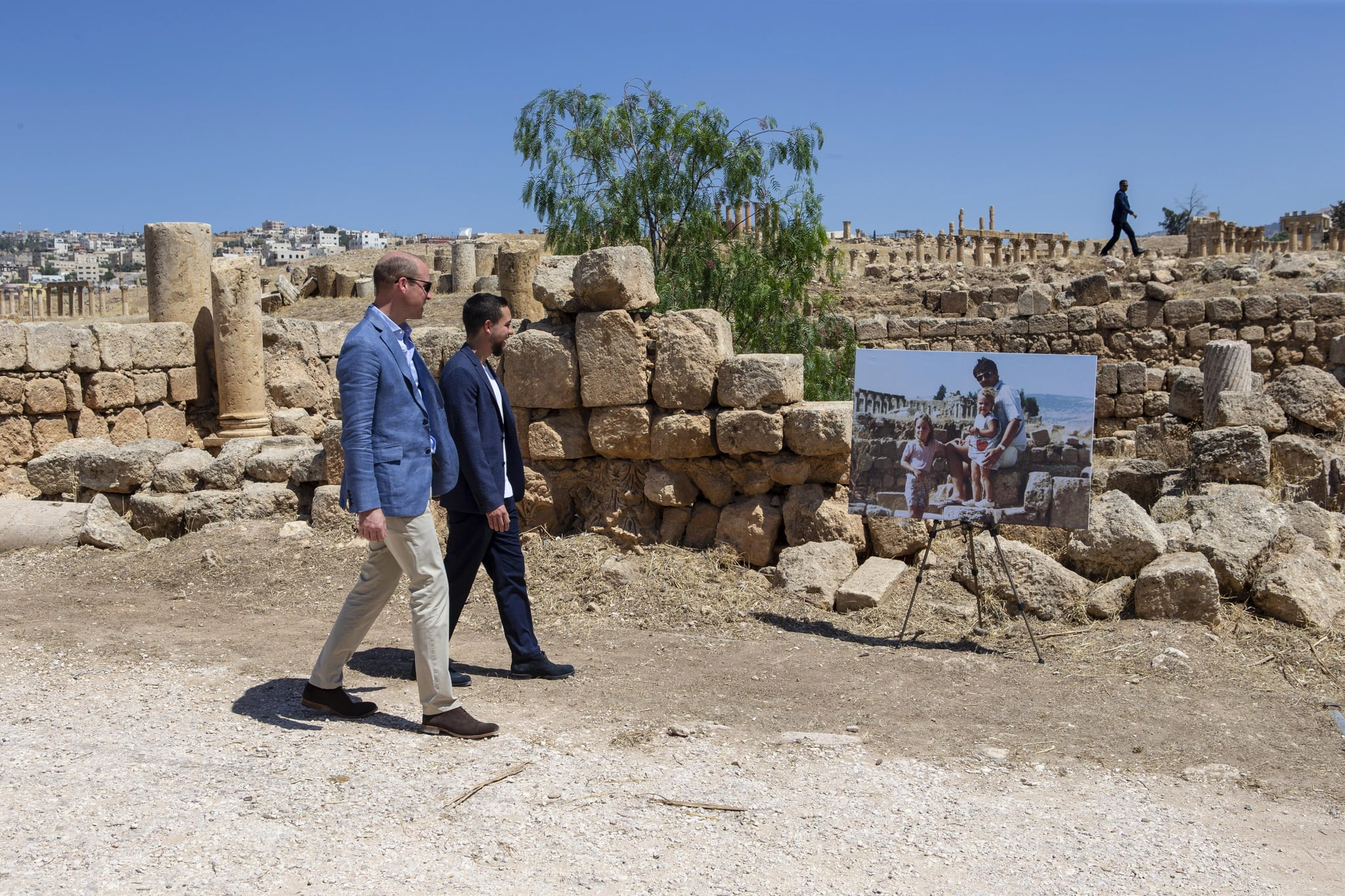 AMMAN, JORDAN - JUNE 25: Prince William, Duke of Cambridge and Crown Prince Hussein of Jordan walk past an enlarged photo of Catherine, Duchess of Cambridge in her youth with her father on a family holiday, as they visit the Jerash archaeological site on June 25, 2018 in Amman, Jordan. (Photo by Ian Vogler - Pool/Getty Images)
