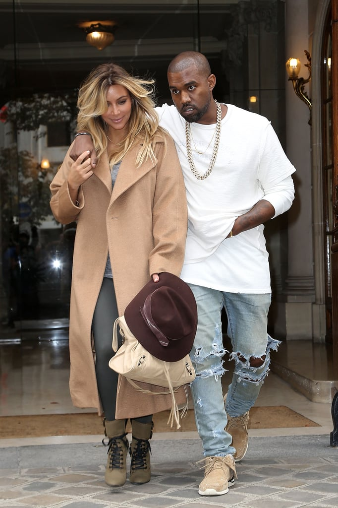 Kim Kardashian and Kanye West walked hand in hand in Paris the day they arrived, with Kim sporting a tan overcoat with gray leggings.