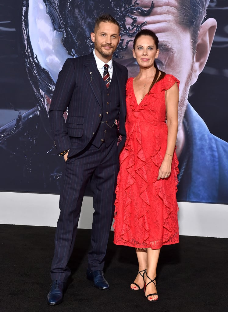 Tom Hardy was looking significantly less possessed by an amorphous alien symbiote at the premiere of Venom on Monday. His apparent affinity for playing characters that wear masks in movies can sometimes make us forget how gorgeous he is, but thankfully his red carpet appearances remind us of his alluring smile and smolder. He was accompanied by many of his fellow Venom castmates, including Michelle Williams, Kelly Marcel, Riz Ahmed, and Jenny Slate.  Although the movie hasn't officially hit theaters yet, there have already been talks about a sequel and spinoffs. We're definitely hoping that the film delivers at the box office, and not because we want to see more of Tom Hardy, but because — OK, it's because we want to see more of Tom Hardy.  View pictures of Tom and the other stars of Venom in the photos ahead.