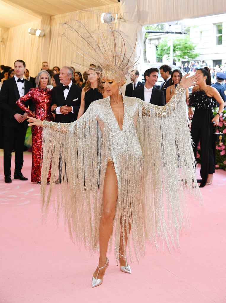 "If you were a little confused about this year's ""Camp"" theme at the Met Gala, Celine Dion totally feels your pain. During the red carpet, the iconic singer admitted to E! News that she wasn't entirely sure what to expect at first. ""I thought, like, 'Camping? We're going camping!'"" LOL! In the end, she interpreted it as ""luxurious, antique, and timeless."" Well, based on her stunning outfit, she definitely accomplished just that. Celine popped up on the pink carpet looking like a dancer from The Rockettes as she rocked a fringe dress and matching feather hat. See her stunning appearance ahead.       Related:                                                                                                           These Met Gala Looks Are Dramatic Enough to Entertain You For the Rest of the Year"