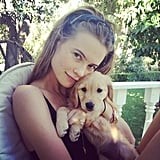 Behati Prinsloo cuddled with an adorable golden retriever puppy. Source: Instagram user behatiiprinsloo