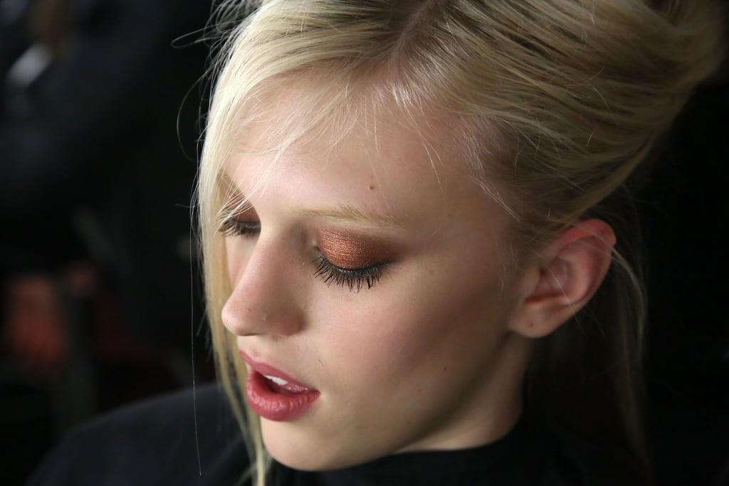 But the eyes were the showstopper. Westman layered ColorStay Shadow Stick in Atomic and Torch to achieve the bold copper color. Right before the runway, she created a wet finish by adding a touch of gloss on the lids.