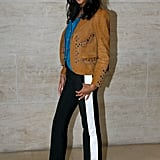 Wearing a denim blouse, suede jacket, and striped pants all by Louis Vuitton.