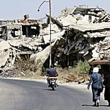Civilians walk past rubble in the Western Syrian city Homs.