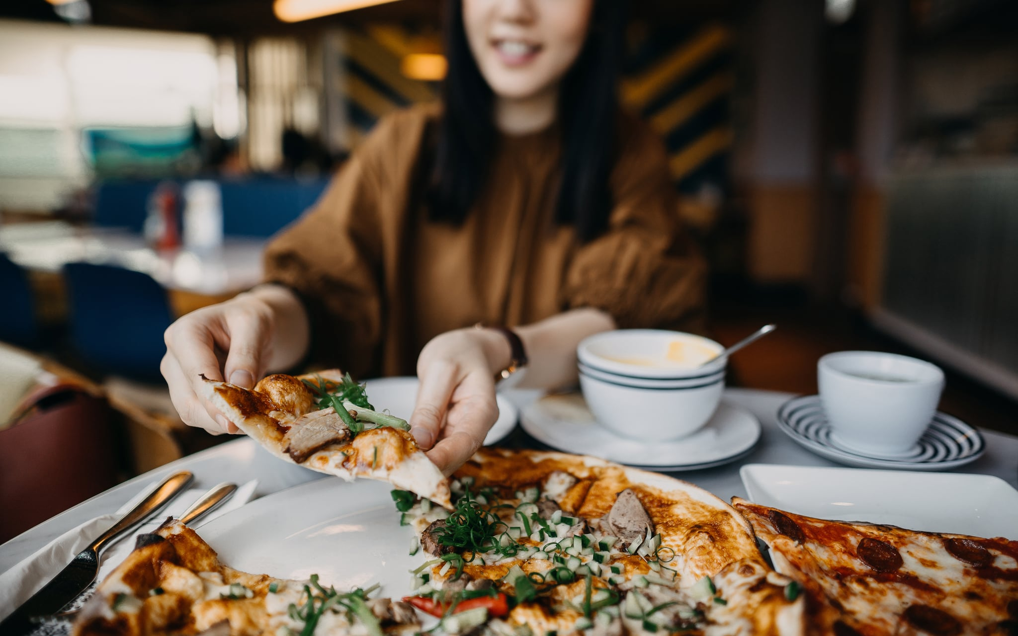 Close up of young woman enjoying meal and eating freshly made pizza in a restaurant
