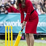 The duchess showed off her cricket skills in an unexpectedly polished red ensemble while at Latimer Square Gardens.