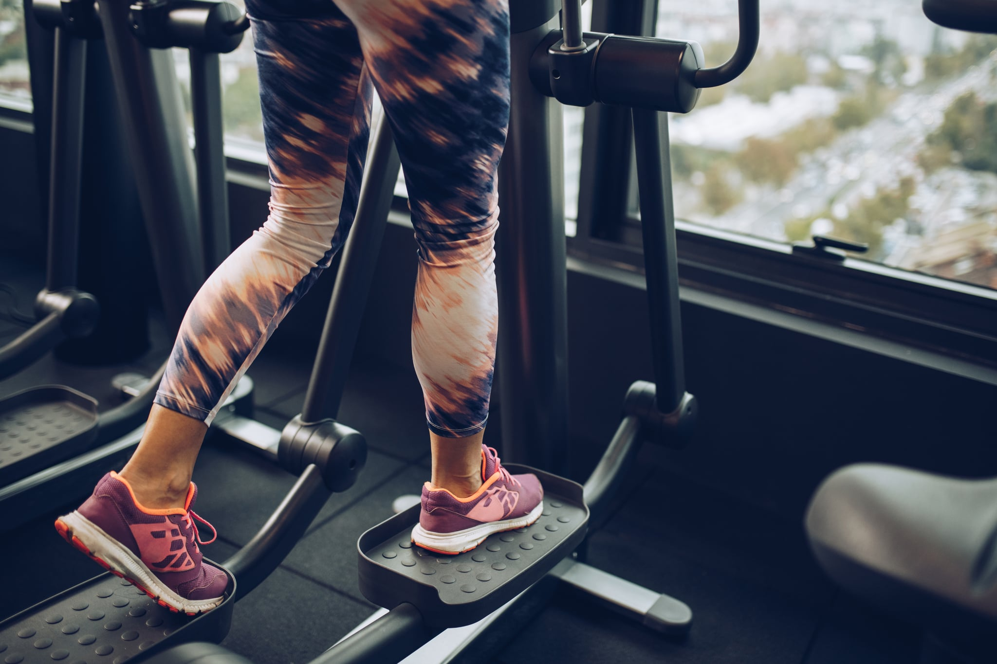 Unrecognisable athlete's legs during warm up on a cross trainer in a gym.