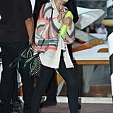Ashley Benson wore a slick mix of cool-girl separates, including a striped cardigan, studded bag, cap-toe flats, and a yellow neon clutch.