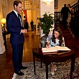 Prince William smiled as Kate Middleton signed a guest book during a British gala at Eden Hall in Singapore.
