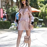 If your dress is a feminine style, go the complete opposite with your footwear. Aimee Song wore a pair of edgy, buckled ankle boots with her ruffled pink minidress for that cool-girl feel.