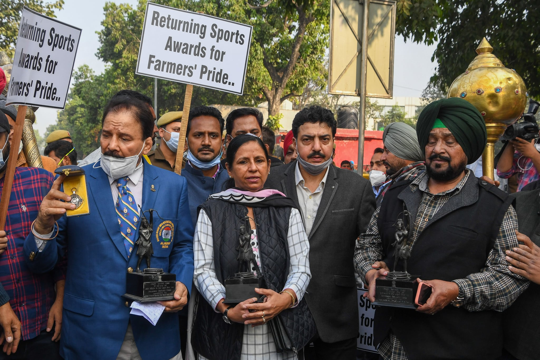 Former wrestler Kartar Singh (R) and former field hockey players Jasbir Kaur (C) and Gurmail Singh (R) pose with their trophies as they march to the the President's house to return their awards in support of the farmer's protest against the recent agricultural reforms, in New Delhi on December 7, 2020. (Photo by Prakash SINGH / AFP) (Photo by PRAKASH SINGH/AFP via Getty Images)