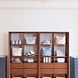 A mid-century modern bookcase is the perfect spot for accessories, like hats and tote bags. Cuyana's signature orange boxes add the perfect pop of color on the bottom shelf.