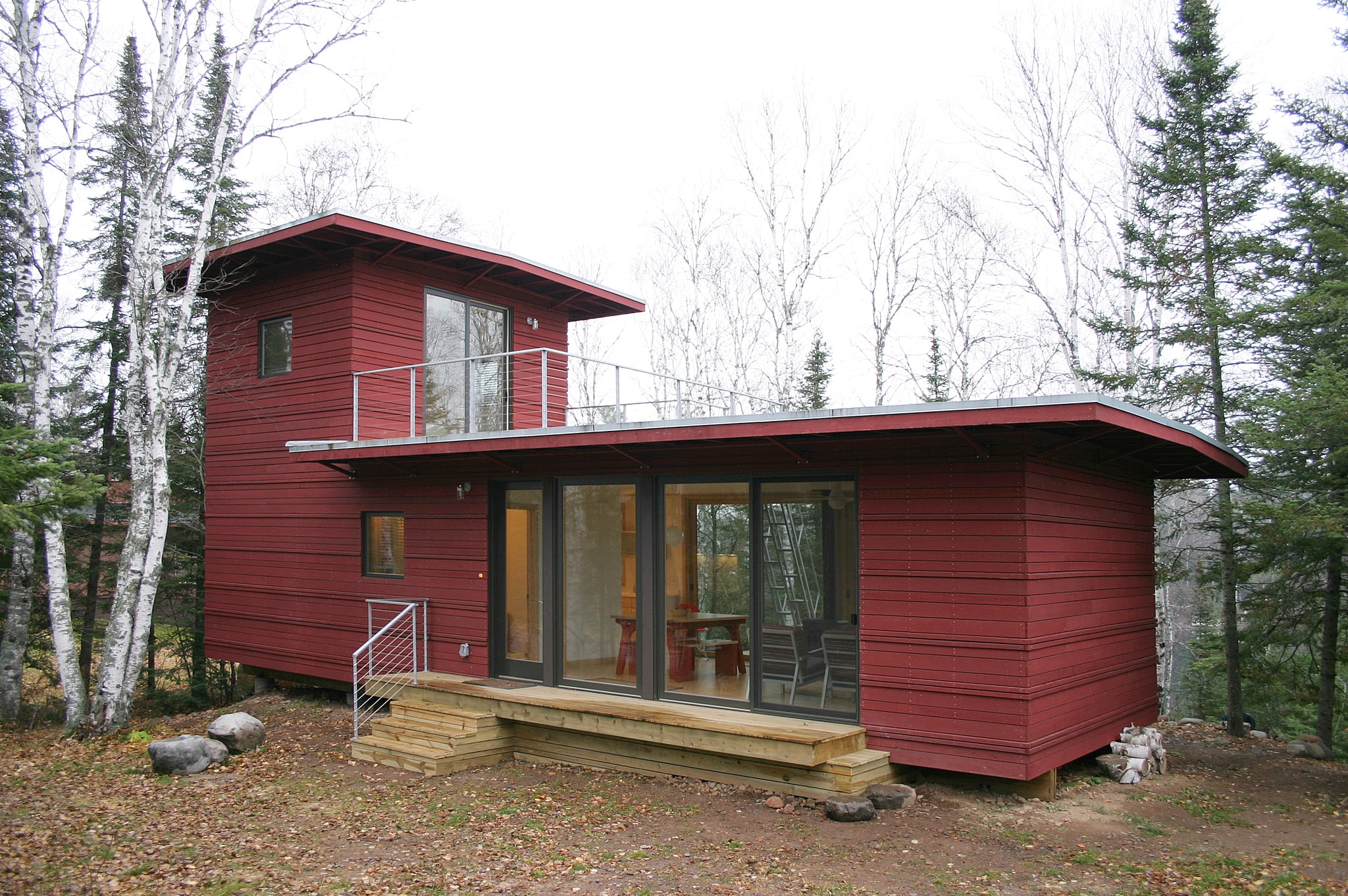The McGlasson weeHouse boasts a rooftop deck, gorgeous forest views, and a price far below $200,000 — talk about a dream home! The gorgeous red exterior is just the start of this tiny dwelling's beautiful features; it also includes a modern kitchen, huge windows, and panoramic views of evergreen trees from its back deck.