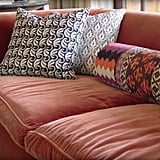 John has had his orange couch for 13 years, and it's outfitted with patterned pillows.