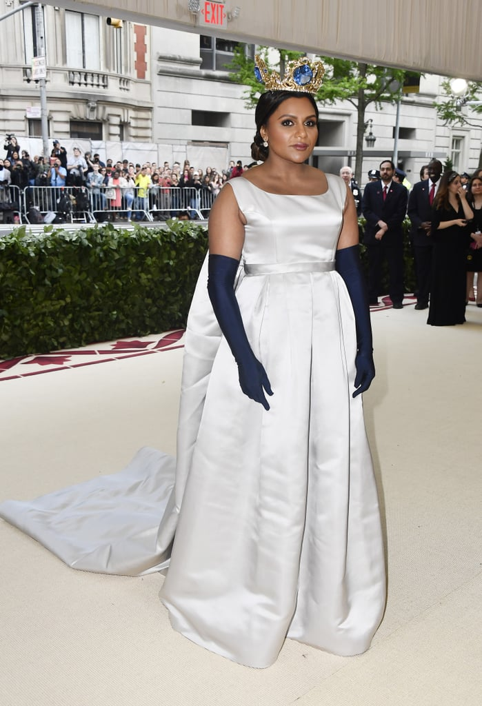 "Mindy Kaling waltzed into the 2018 Met Gala like the queen that she is. The 38-year-old actress arrived at the very exclusive, high-drama event in a silver Vassilis Zoulias gown and navy elbow-length gloves. Tying in the religious — and slightly medieval — ""Heavenly Bodies"" theme, Mindy wore an opulent crown with massive blue jewels.  Though Mindy has attended the Met Gala several times years prior, this is her first time since filming Ocean's 8, which is primarily centred on the event! With her other costars in attendance — ahem, Rihanna — it looks like the gang is back together for fashion's biggest night.       Related:                                                                                                           Every Look at This Year's Met Gala Is Bold Enough to Leave an Impression"