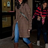 Zoe Saldana kept her Winter outfit in the brown family with a brown plaid coat, contrasting lightwash jeans, and brown leather boots.