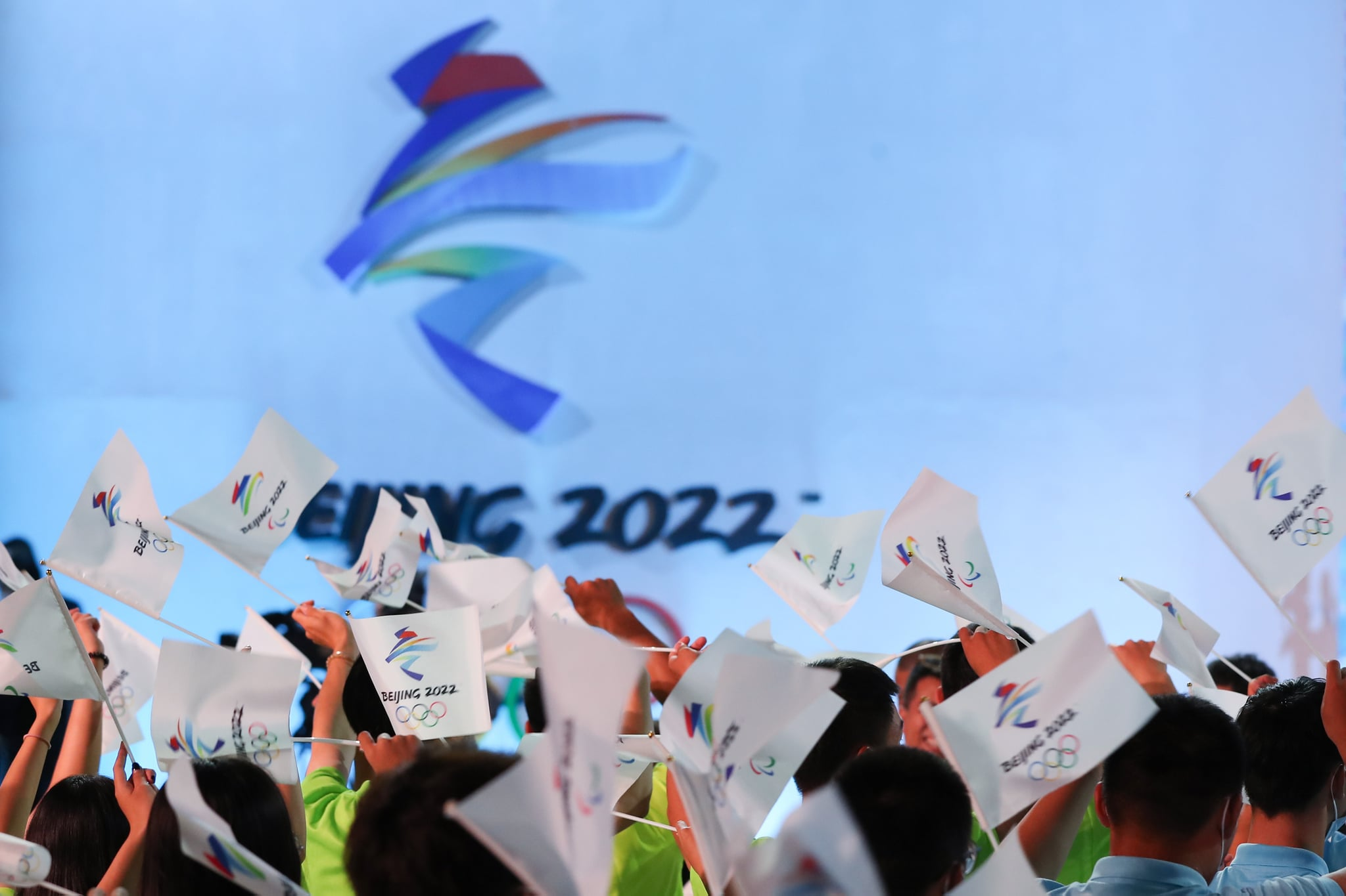 BEIJING, CHINA - SEPTEMBER 17: People wave flags of the Beijing 2022 Winter Olympic Games during the Beijing 2022 Winter Olympic & Paralympic Games Motto Launch Ceremony on September 17, 2021 in Beijing, China. (Photo by Emmanuel Wong/Getty Images)
