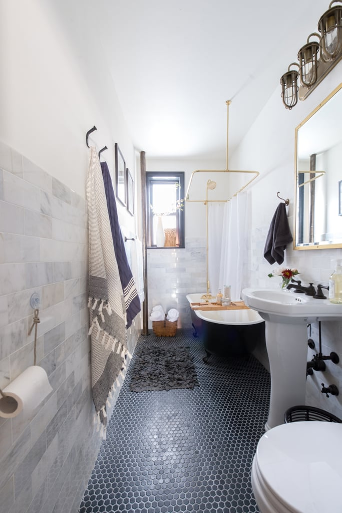 Limiting the palette to two or three colours and playing with texture helped make the small bathroom appear to be much larger. Marble subway tiles on the wall and black tiles with light grouting on the floor add subtle pattern and richness.  Photo by Samantha Goh via Homepolish