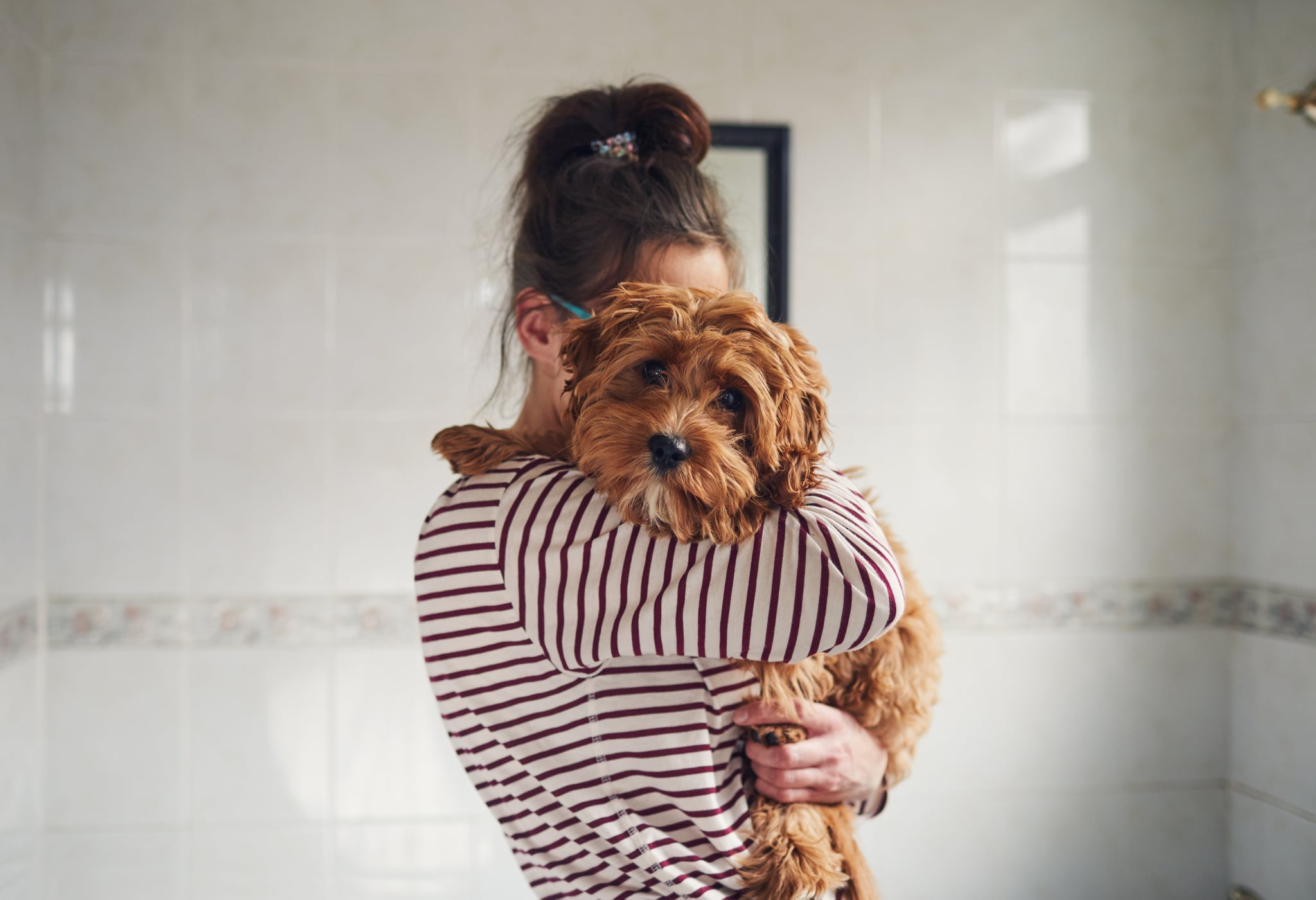 Woman holding her puppy over the shoulder