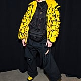 Posing backstage at Prabal Gurung's show wearing a neon yellow puffer, jumpsuit, and black and yellow boots by A.F. Vandevorst. She styled her look with a Prada waist bag.