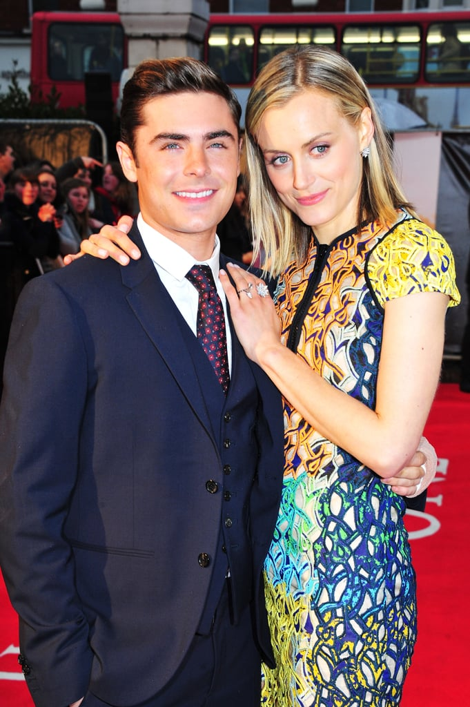 "Zac Efron and his The Lucky One love interest Taylor Schilling were in London today for the European premiere of the Nicholas Sparks movie. Taylor wore a bright Peter Pilotto dress and peek-a-boo Rupert Sanderson heels for the occasion, while Zac dressed up in a sharp suit but appeared to be nursing a hand injury, with a bandage wrapped around one of his palms. Zac and Taylor's film hit theaters in the USA this weekend and made a strong showing at the box office, taking the second-place position. In the lead, though, was the romantic comedy Think Like a Man. The two love-themed films combined to finally knock The Hunger Games out of the leading spot after a solid month at the top. Some of The Lucky One's ticket-sales success might be due to Zac's work promoting the film in recent weeks. He graces the new cover of Men's Health and made several TV appearances, including a comical visit to Jimmy Kimmel Live, during which Jimmy put Zac's bra-unhooking skills to the test and got him to reveal his ""musical theater geek"" side."