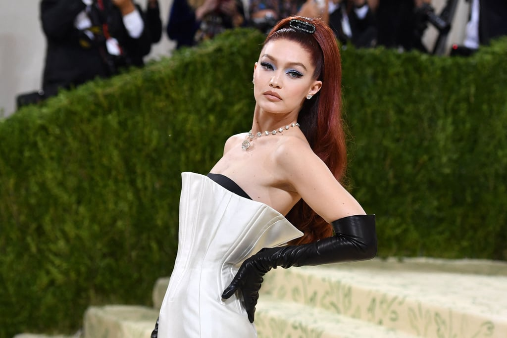 Gigi Hadid switched things up for her sixth appearance at the 2021 Met Gala. The model arrived at the star-studded event with her hair in a dark auburn shade that was quite the departure from her usual blond. Hadid actually dyed her hair red in March after being inspired by Anya Taylor-Joy's character on The Queen's Gambit, but that was more of a copper color, and in recent weeks, it faded back a bit to her natural base.  Hadid's hair was styled in a voluminous ponytail adorned with a black Prada barrette, which matched her white corset dress and black elbow-length gloves, also by Prada. For her makeup, Hadid wore blue eyeshadow and a classic cat eye. Take a gander at her beauty look ahead.