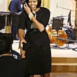 She paired a cool green-and-white polka-dot blouse with a black pencil skirt and black cardigan. The stack of pearl bracelets gave the FLOTUS an extra boost of classic elegance.