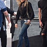 Jen styled a gold chainstrap shoulder bag with bootcut jeans and boots for an outing in LA in December 2017.