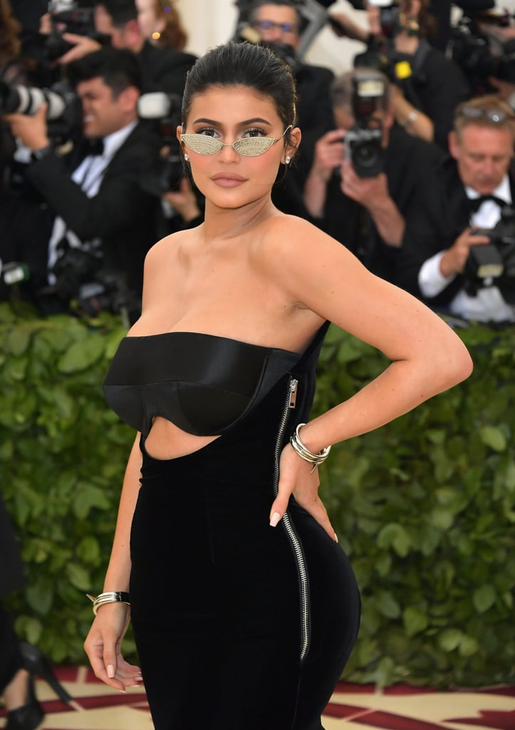 "Kylie Jenner went her own way at the 2018 Met Gala. Despite the opulent ""Heavenly Bodies"" theme, the 20-year-old makeup mogul and new mom wore a futuristic Alexander Wang gown and tiny '90s-style sunglasses, which appear to have embellishments on the actual lenses. Kylie posed with her boyfriend, Travis Scott, and the exclusive event marked the couple's first red carpet appearance since welcoming their daughter, Stormi, in February. The gala was a real family affair with Kendall Jenner, Kris Jenner, and Kim Kardashian all in attendance — each representing different brands, no less. Ahead, see pictures of Kylie's supermodern ensemble."