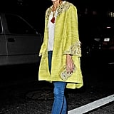 Spotted: Olivia embodying Spring warmth in an embellished yellow Marchesa coat, white brocade blouse, and statement necklace at the brand's show at NYFW.