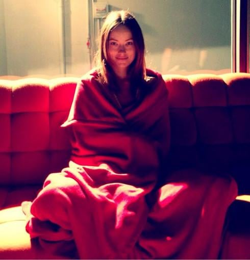 Olivia Wilde wrapped herself in a blanket — despite the 105-degree temperatures on set. Source: Twitter user oliviawilde