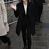 During the day, Emma  teamed a black coat and skinnies with brown boots.