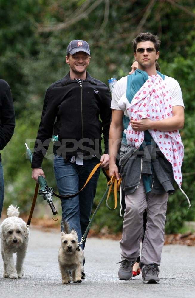 Neil Patrick Harris and David Burtka took their twins and dogs on a stroll with friends around their LA neighborhood yesterday. Three-month-old Gideon and Harper were tightly bundled in their dads' chests for the outing, not yet showing off their little faces. NPH has been settling into fatherhood and enjoying the babies' fun milestones, like laughing, while also juggling work and social obligations since their birth in October. He did, though, step out with David for an art event last week and also filmed a new episode of How I Met Your Mother with a cameo by Katy Perry.