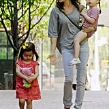 For a day out with her girls, Sarah Jessica Parker donned form-fitted gray jeans. To dress up the outfit, she added a pop of red via Swedish Hasbeens sandals.