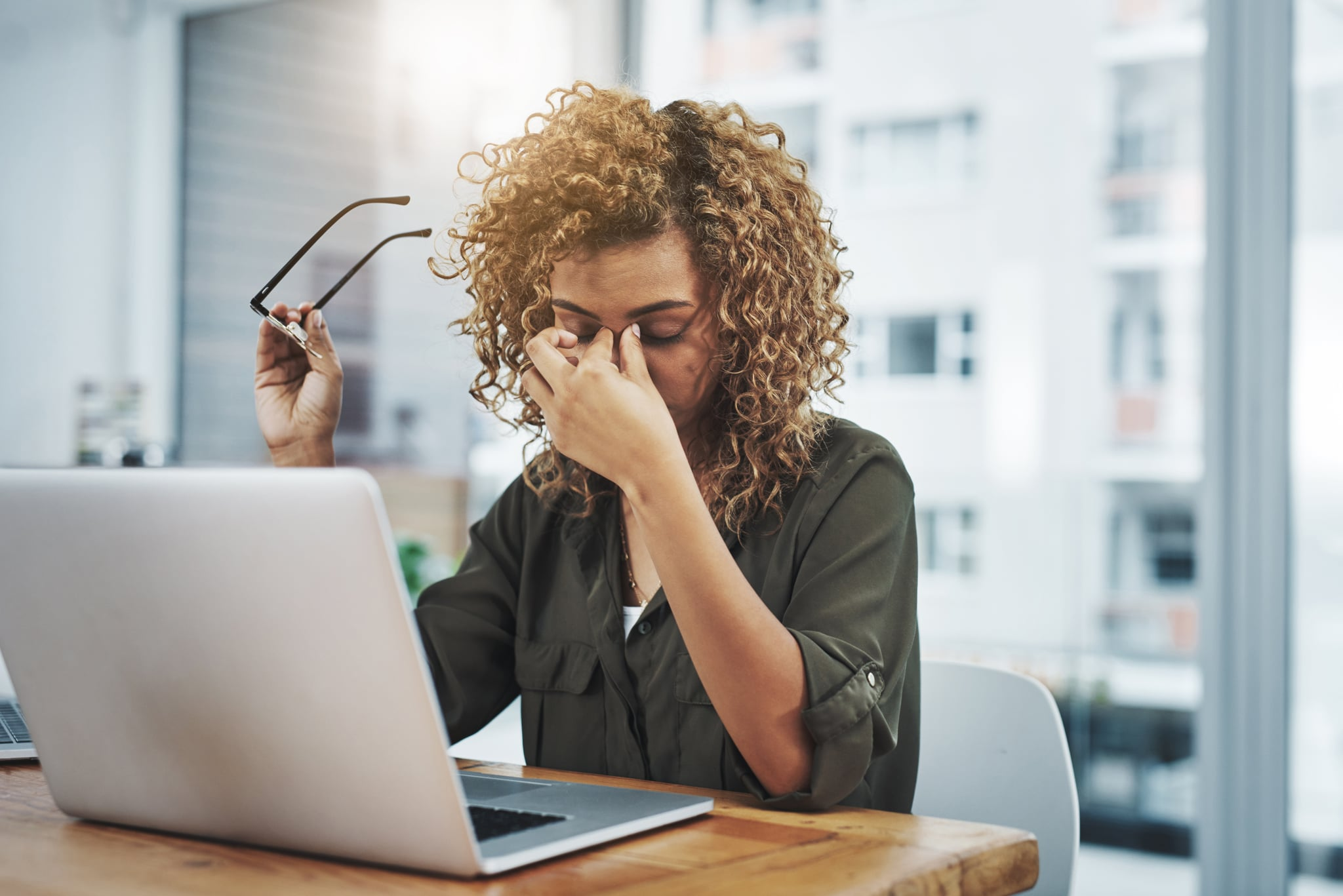 Shot of a young woman suffering from stress while using a computer at her work desk