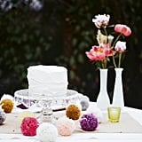 Instead of adding flowers directly to the cake, keep it plain and place vases with tall, blooming peonies and roses next to the cake stand.